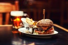 Άνθρωποι που και που πίνουν στο αμερικανικό εστιατόριο, την μπύρα, το χάμπουργκερ, το κρασί και άλλα αμερικανικά specialites στοκ εικόνες