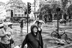 Άνθρωποι που καλύπτουν από τη βροχή στο Λονδίνο στοκ φωτογραφία