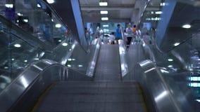 Άνθρωποι που κινούνται στις επίπεδες κυλιόμενες σκάλες σε ένα τερματικό ή έναν σταθμό τρένου αερολιμένων κίνηση αργή φιλμ μικρού μήκους