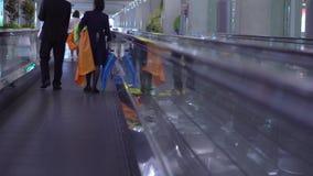 Άνθρωποι που κινούνται στις επίπεδες κυλιόμενες σκάλες σε ένα τερματικό ή έναν σταθμό τρένου αερολιμένων απόθεμα βίντεο