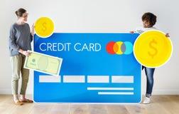 Άνθρωποι που κρατούν τα εικονίδια πιστωτικών καρτών και χρημάτων Στοκ Εικόνες
