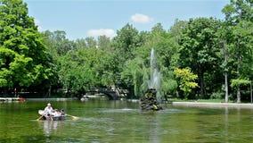 Άνθρωποι που κωπηλατούν τη βάρκα στους κήπους Cismigiu στο Βουκουρέστι φιλμ μικρού μήκους