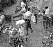 Άνθρωποι που μεταφέρουν εμπορεύματα στα κεφάλια τους Στοκ Εικόνες