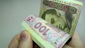 Άνθρωποι που μετρούν τους εκατό λογαριασμούς hryvnia σε έναν πίνακα απόθεμα βίντεο