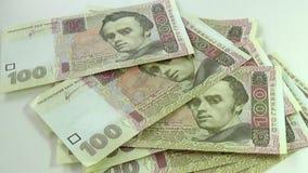 Άνθρωποι που μετρούν τους εκατό λογαριασμούς hryvnia σε έναν πίνακα φιλμ μικρού μήκους