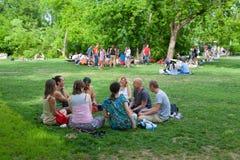 Άνθρωποι που μιλούν και που κάθονται στο χορτοτάπητα Στοκ φωτογραφία με δικαίωμα ελεύθερης χρήσης