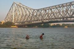 Άνθρωποι που λούζουν στον ποταμό hooghly κοντά στη γέφυρα του Howrah, Kolkata Στοκ Εικόνες