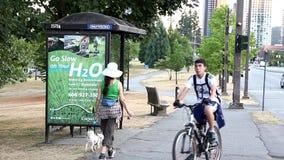 Άνθρωποι που οδηγούν το ποδήλατο εκτός από τη στάση λεωφορείου απόθεμα βίντεο