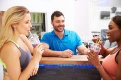 Άνθρωποι που πίνουν τα πρωτεϊνικά κουνήματα στο φραγμό ικανότητας σε μια γυμναστική Στοκ εικόνες με δικαίωμα ελεύθερης χρήσης