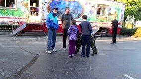 Άνθρωποι που παίζουν με το σκυλί στις διασκεδάσεις καρναβάλι δυτικών ακτών φιλμ μικρού μήκους