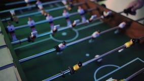 Άνθρωποι που παίζουν στο επιτραπέζιο ποδόσφαιρο ή kicker με τους μικροσκοπικούς φορείς απόθεμα βίντεο