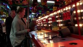Άνθρωποι που παίζουν whack gameat τις διασκεδάσεις καρναβάλι φιλμ μικρού μήκους