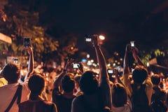 Άνθρωποι που παίρνουν τη φωτογραφία στο μέτωπο με το υπαίθριο υπόβαθρο νύχτας στοκ εικόνες