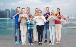 Άνθρωποι που παρουσιάζουν σημάδι χεριών καρδιών πέρα από την ακτή πόλεων Στοκ Εικόνες