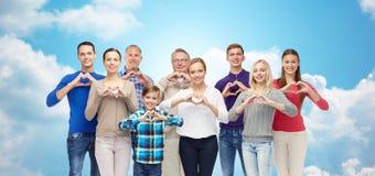 Άνθρωποι που παρουσιάζουν σημάδι χεριών καρδιών πέρα από τον ουρανό και τα σύννεφα Στοκ Φωτογραφίες