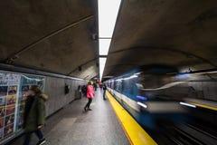 Άνθρωποι που περιμένουν έναν υπόγειο Cote des Neiges στην πλατφόρμα σταθμών, μπλε γραμμή, ενώ ένα τραίνο μετρό έρχεται, με μια θα στοκ εικόνες με δικαίωμα ελεύθερης χρήσης