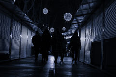Άνθρωποι που περπατούν κάτω από μια οδό με τα καταστήματα κλειστά Στοκ Φωτογραφία