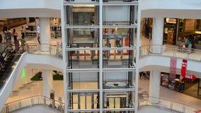 Άνθρωποι που περπατούν και κυλιόμενη σκάλα χρήσης για να κινηθεί πάνω-κάτω για τις αγορές φιλμ μικρού μήκους