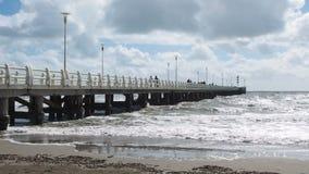 Άνθρωποι που περπατούν στην αποβάθρα Marmi dei Forte ενώ τα μεγάλα κύματα κρύβονται στην παραλία απόθεμα βίντεο