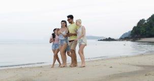 Άνθρωποι που περπατούν στην παραλία που χρησιμοποιεί την έξυπνη τηλεφωνική σε απευθείας σύνδεση ομιλία κυττάρων, νέα ομάδα τουρισ απόθεμα βίντεο
