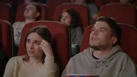 Άνθρωποι που προσέχουν τη τρομακτική ταινία στη κινηματογραφική αίθουσα Νεαρός άνδρας που ψεκάζει popcorn απόθεμα βίντεο