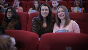 Άνθρωποι που προσέχουν τον κινηματογράφο κωμωδίας στον κινηματογράφο απόθεμα βίντεο