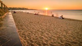 Άνθρωποι που προσέχουν το ηλιοβασίλεμα στην παραλία σε Frankston, Αυστραλία, ζουμ μέσα απόθεμα βίντεο