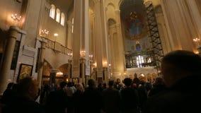 Άνθρωποι που προσεύχονται στη λειτουργία στον ιερό καθεδρικό ναό τριάδας στο Tbilisi, χριστιανική πίστη απόθεμα βίντεο