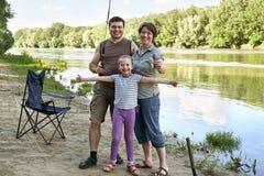 Άνθρωποι που στρατοπεδεύουν και που αλιεύουν, οικογένεια ενεργοί στη φύση, αλιεία στο δόλωμα, ποταμός και δασικός, θερινή περίοδο Στοκ εικόνα με δικαίωμα ελεύθερης χρήσης
