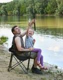 Άνθρωποι που στρατοπεδεύουν και που αλιεύουν, οικογενειακός ελεύθερος χρόνος στη φύση, αλιεία στο δόλωμα, ποταμός και δασικός, θε Στοκ Εικόνα
