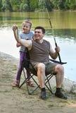 Άνθρωποι που στρατοπεδεύουν και που αλιεύουν, οικογενειακός ελεύθερος χρόνος στη φύση, αλιεία στο δόλωμα, ποταμός και δασικός, θε Στοκ εικόνα με δικαίωμα ελεύθερης χρήσης