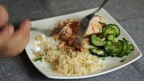 Άνθρωποι που τρώνε τα ψάρια σολομών με το ρύζι και το αγγούρι απόθεμα βίντεο
