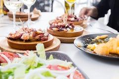 Άνθρωποι που τρώνε το pulpo ένα Λα gallega Της Γαλικίας μαγειρευμένο ύφος χταπόδι με τις πατάτες, το ελαιόλαδο πάπρικας και Στοκ Φωτογραφίες