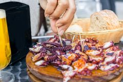 Άνθρωποι που τρώνε Pulpo ένα ξύλινο πιάτο Λα Gallega Της Γαλικίας μαγειρευμένο ύφος χταπόδι με το ελαιόλαδο πάπρικας και Στοκ φωτογραφία με δικαίωμα ελεύθερης χρήσης
