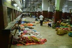 Άνθρωποι που τυλίγονται στα καλύμματα που κοιμούνται στο σιδηροδρομικό σταθμό Στοκ Εικόνες