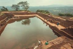 Άνθρωποι που χαλαρώνουν γύρω από την αρχαία λίμνη της πόλης Sigiriya με τις καταστροφές και τη archeological περιοχή Στοκ Φωτογραφίες