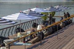 Άνθρωποι που χαλαρώνουν κάτω από τις ομπρέλες θαλάσσης Στοκ Εικόνες
