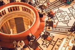 Άνθρωποι που χαλαρώνουν και που πίνουν τον καφέ μέσα στον καφέ με τα ιστορικά έπιπλα Στοκ Εικόνες