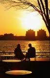 Άνθρωποι που χαλαρώνουν στον ποταμό του Hudson ηλιοβασιλέματος Στοκ Φωτογραφία