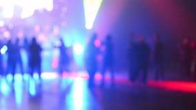 Άνθρωποι που χορεύουν κατά τη διάρκεια του κόμματος disco κάτω από τα ζωηρόχρωμα φω'τα απόθεμα βίντεο