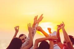 Άνθρωποι που χορεύουν στην παραλία με τα χέρια επάνω έννοια για το κόμμα, τη μουσική και τους ανθρώπους στοκ εικόνα