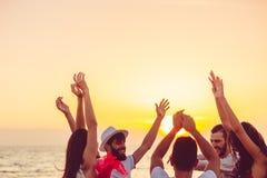 Άνθρωποι που χορεύουν στην παραλία με τα χέρια επάνω έννοια για το κόμμα, τη μουσική και τους ανθρώπους στοκ εικόνα με δικαίωμα ελεύθερης χρήσης