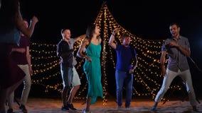 Άνθρωποι που χορεύουν στο κόμμα παραλιών νύχτας απόθεμα βίντεο