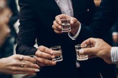 Άνθρωποι που ψήνουν τα ποτήρια εκμετάλλευσης της βότκας ενθαρρυντικά στο γάμο REC στοκ εικόνα με δικαίωμα ελεύθερης χρήσης