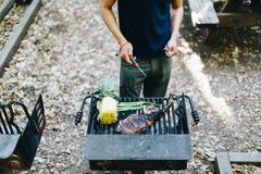 Άνθρωποι που ψήνουν τη στρατοπέδευση μπριζολών βόειου κρέατος στη σχάρα Στοκ Εικόνες