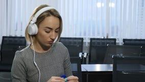 Άνθρωποι, ραπτική, handycraft έννοια Νέα όμορφη γυναίκα στα ακουστικά που πλέκουν με το πλέξιμο της βελόνας και του μπλε νήματος απόθεμα βίντεο