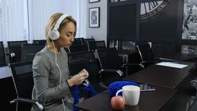 Άνθρωποι, ραπτική, handycraft έννοια Νέα όμορφη γυναίκα στα ακουστικά που πλέκουν με το πλέξιμο της βελόνας και του μπλε νήματος φιλμ μικρού μήκους