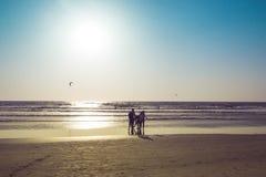 Άνθρωποι σε μια θάλασσα σε ένα ηλιοβασίλεμα, παραλία Arambol, Goa, Ινδία Paraglid Στοκ Εικόνες