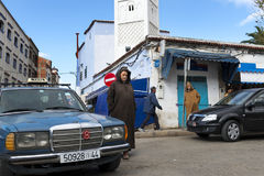 Άνθρωποι σε μια οδό με τα αυτοκίνητα και καταστήματα στην πόλη Chefchaouen στο Μαρόκο, Βόρεια Αφρική Στοκ εικόνες με δικαίωμα ελεύθερης χρήσης