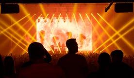 Άνθρωποι σκιαγραφιών στη συναυλία, ηλεκτρονική μουσική χορού, κίτρινο lig στοκ φωτογραφίες